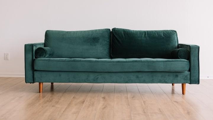 sofa-verde-sobre-suelo-de-madera